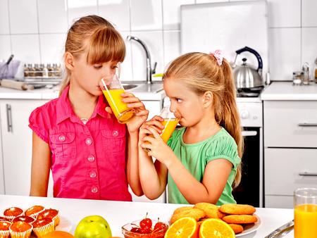 ni�os desayuno: Desayuno feliz de los ni�os en la cocina y beber jugo de naranja. Foto de archivo