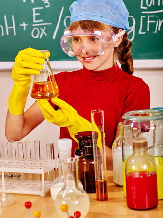 chemistry class: Teenager girl holding flask in chemistry class.