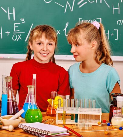 chemistry class: Happy two girl holding flask in chemistry class. Stock Photo