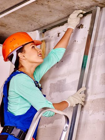 foremaster: Happy woman in builder uniform and orange helmet at work.