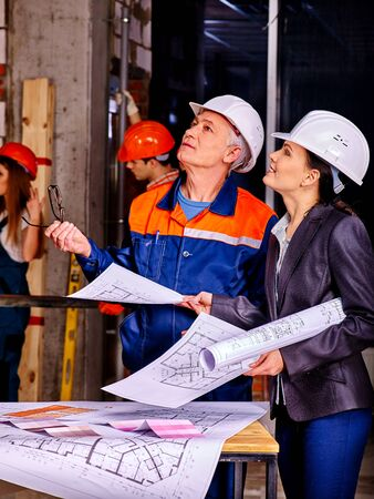 old building: Business woman  and man in builder helmet looking up . Elderly man teaches young girl