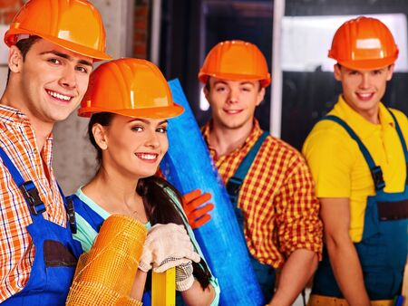 Happy group people in builder uniform. Four people. Stock Photo