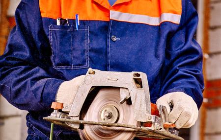 circular saw: Hands of man  builder holding circular saw.