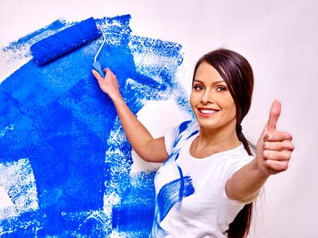 Bonne mur de peinture de femme à la maison et en montrant le pouce en place. Banque d'images - 39838058