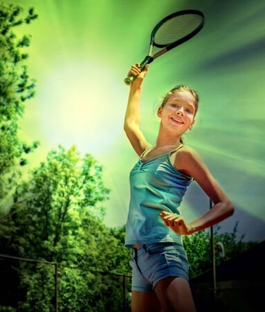 teener: Girl sportsman with racket and ball in the sun and green trees. Toned image.
