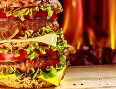 double oven: Double patty hamburger on wooden board on background of fire.