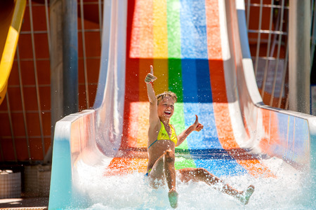 child playing: Happy child girl in bikini showing thumb up sliding water park.