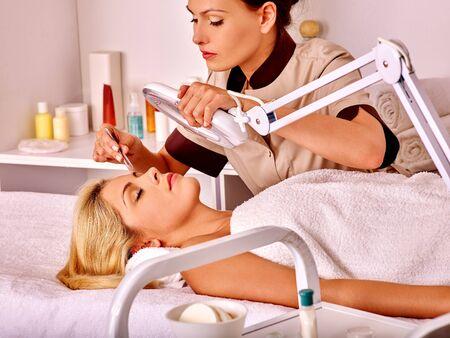 tweezing: Woman getting tweezing eyebrow in beauty salon. Stock Photo