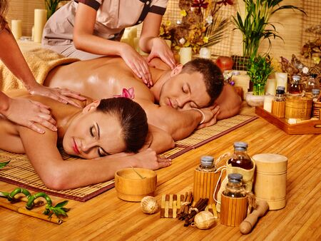 Man and woman relaxing in bamboo spa getting massage. photo
