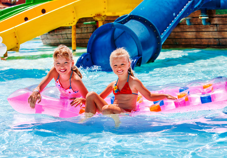 kids playing water: Kids are floating on inflatable mattress in water park. Summer holiday.