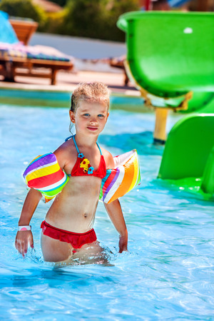 armbands: Child in reb bikini with armbands playing in swimming pool.