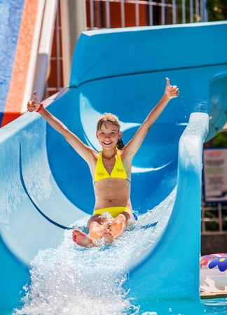 Child hand up on water slide at aquapark. Summer holiday.
