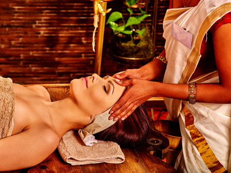 massage herbal: Woman having facial  ayurveda spa treatment in Indian salon. Stock Photo