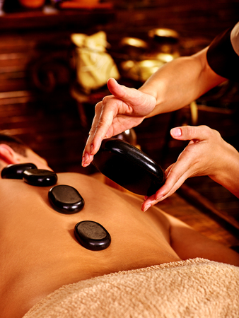 lastone: Man  having lastone Ayurveda spa treatment. Body part. Stock Photo