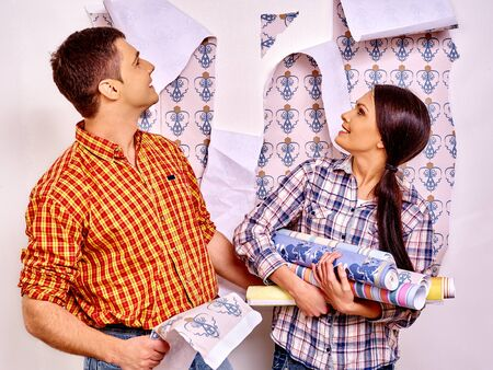 Happy family glues wallpaper and looking up at home. Stock Photo
