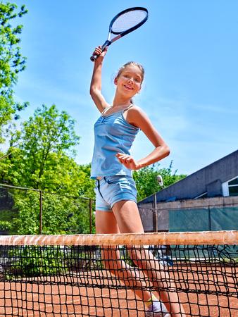 Tienermeisje sportman met racket sprong in de buurt net op de tennisbaan. Stockfoto