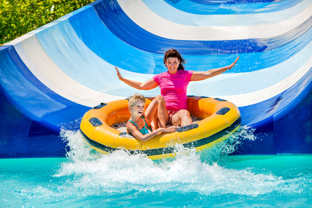 Child with mother on water slide at aquapark. Two persons on summer holiday.