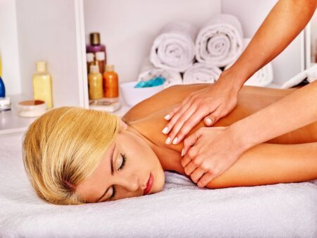 massage: Blond sleeping woman getting massage in health resort. Stock Photo