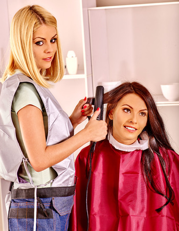 curler: Woman with long hair at hairdresser with iron hair curler.