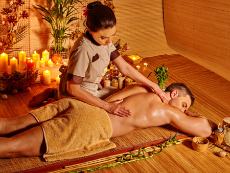 homme massage: Man obtenir des massages dans le spa avec des bougies allumées. Banque d'images