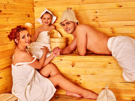 terapia de grupo: Familia con un ni�o con sombrero relajante en la sauna