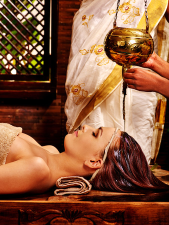 panchakarma: Young woman having head treatment with pouring oil in Ayurveda spa .