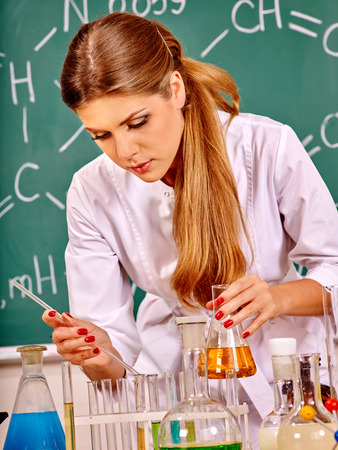 testtube: Chemistry teacher with test-tube working at chemistry classroom. Stock Photo