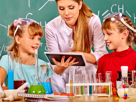 chemistry class: Kids with teacher  holding tablet pc in chemistry class.