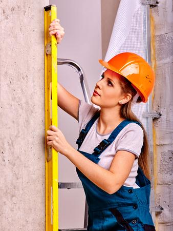 albañil: Mujer feliz con el nivel en el uniforme de un constructor de interior.