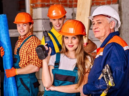 Happy group people in builder uniform looking at camera.