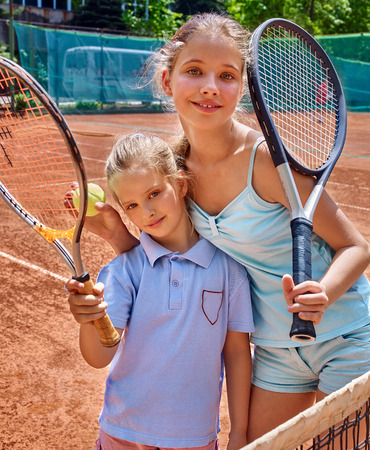 tennis net: Two sport kids girl with racket and ball on  brown tennis court.