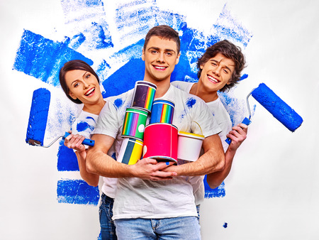 three persons: Happy three persons are painting  wall at home.