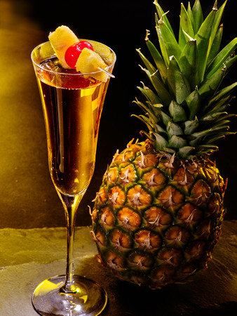 Champagne  cocktail with cherry and whole pineapple with leaves . Cocktail card 59. photo