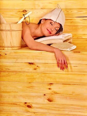 overheating: Young woman lying in sauna. Overheating danger. Stock Photo