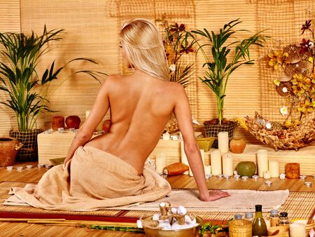bare girl: Young woman getting massage in bamboo spa.