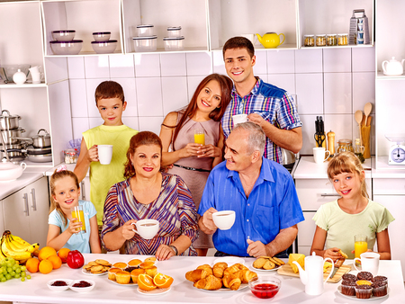 family indoors: Big happy family have breakfast at kitchen. Stock Photo