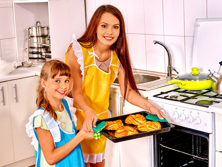 Mother and daughter bake cookies at home kitchen. photo