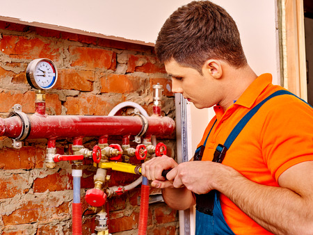 Men builder fixing heating system with special tool. Imagens - 40644708