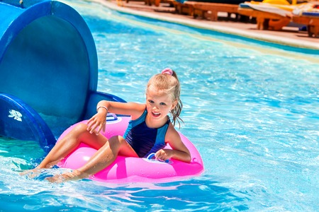float tube: Little girl running with pink inflatable ring. Stock Photo