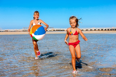 Children holding colored beach ball and running on  water.