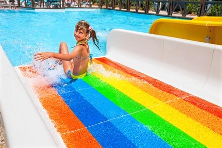 bikini wear: Happy child girl in yellow bikini sliding striped water park.