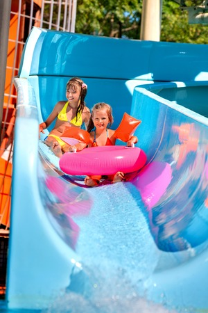 water   slide: Kids on blue water slide at aquapark. Summer holiday. Stock Photo