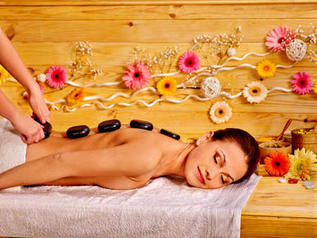 stone therapy: Happy woman getting stone therapy massage in flower wooden spa. Stock Photo