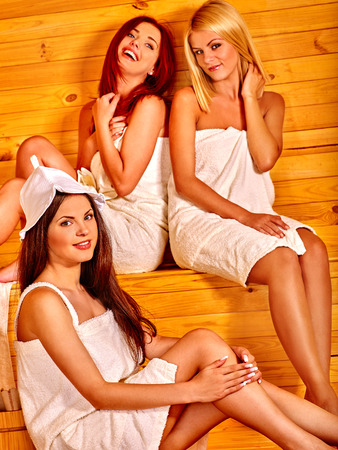 three persons: Group people of three persons relaxing in sauna.