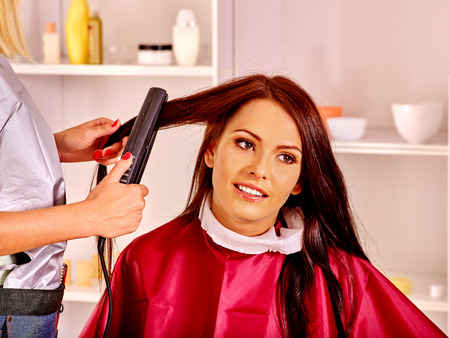 curling irons: Woman at hairdresser with iron hair curler. Hair style.