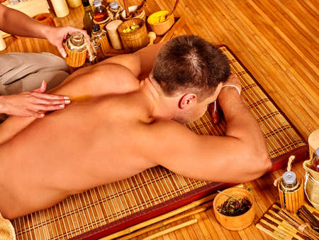 female therapist: Man getting massage  on wooden floor in bamboo spa. Female therapist.