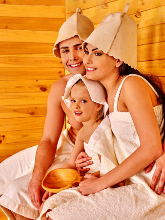 three persons: Family with one kid in hat  relaxing at sauna . Three persons.