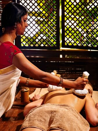 panchakarma: Woman having Ayurveda massage with herbal ball. Open window on background. Stock Photo