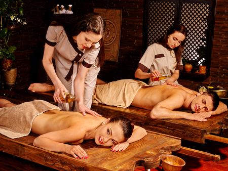 panchakarma: Couple  having oil Ayurveda spa treatment. Two masseuses are making massage.