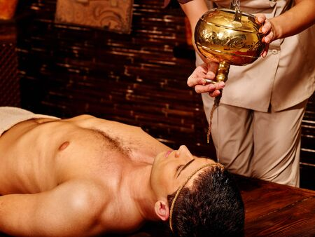 handome: Young  handome man having Ayurveda spa treatment with pouring oil on head.